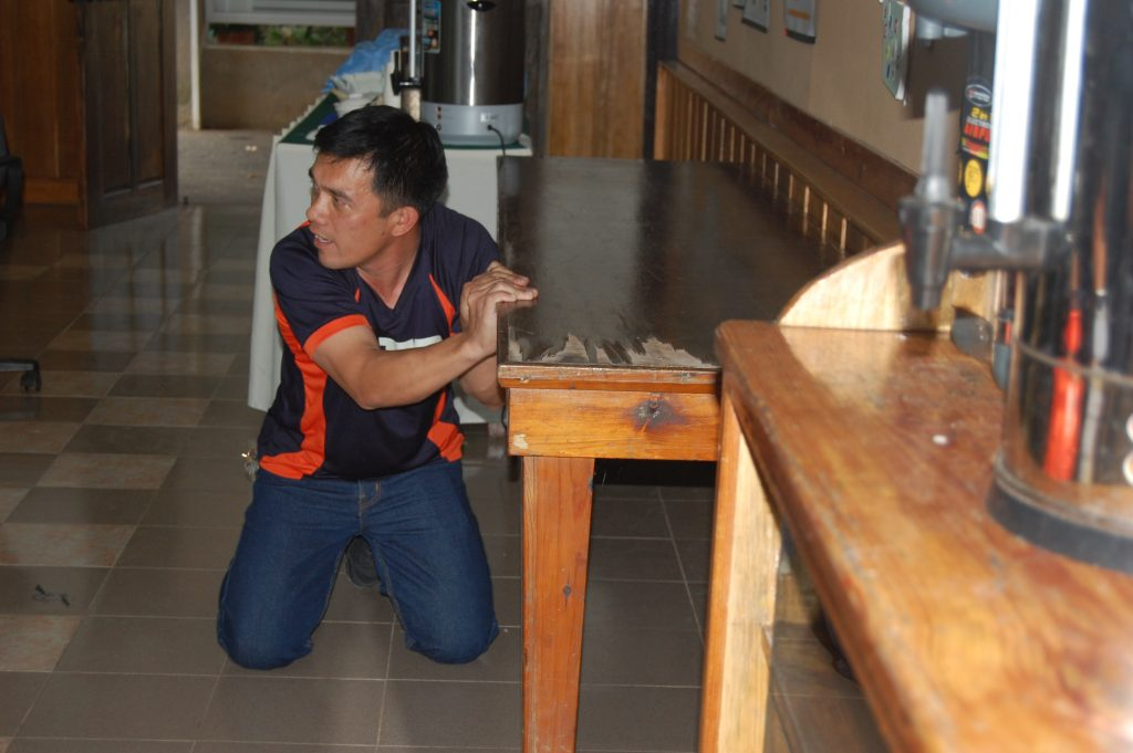 SFO Camilo Balancio of the Baguio City Fire Department giving a demonstration of what to do in case of an earthquake.